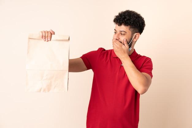 Jeune homme tenant un sac de nourriture à emporter avec surprise et expression du visage choqué