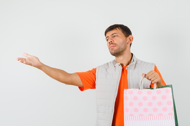 Jeune homme tenant des sacs à provisions, étirant la main en t-shirt, veste, vue de face.