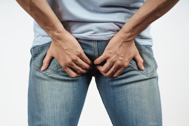 Jeune homme tenant ses fesses à cause de la diarrhée, des hémorroïdes, de la constipation. soins de santé et concept médical.