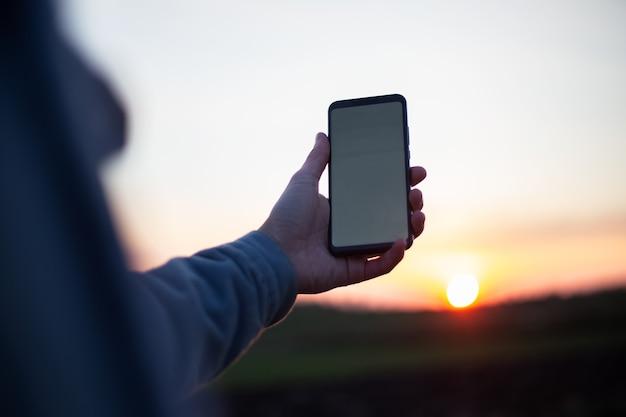 Jeune homme tenant un smartphone avec maquette blanche vide sur fond de coucher de soleil