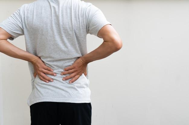 Jeune homme tenant son dos dans la douleur. concept médical