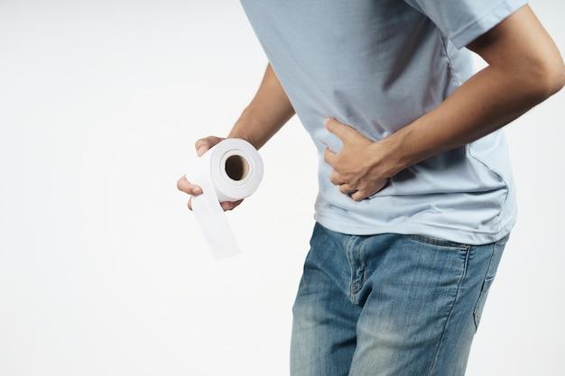Jeune homme tenant son estomac et son papier de soie souffrant de diarrhée, d'incontinence, de prostatite, de maladie vénérienne. concept de soins de santé.