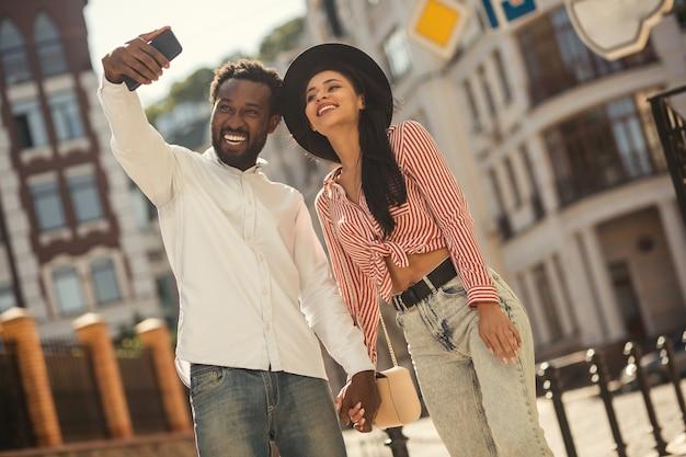 Jeune homme tenant son smartphone moderne et prenant un joli selfie avec sa petite amie dans la rue