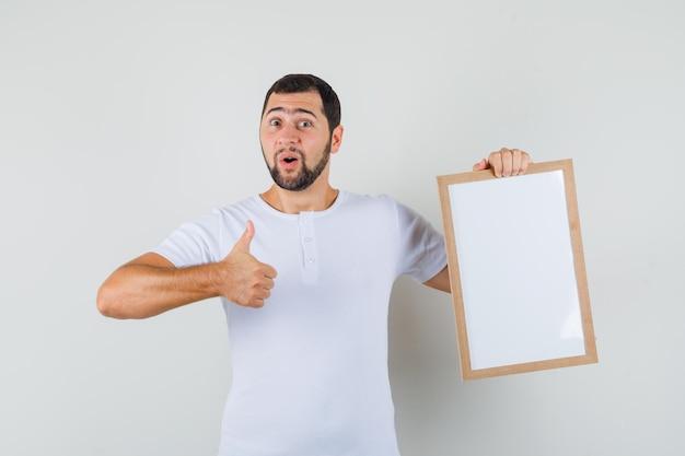 Jeune homme tenant un tableau blanc tout en montrant le pouce en t-shirt et l'air satisfait, vue de face.