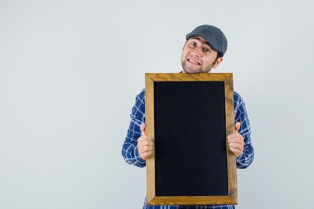 Jeune homme tenant un tableau noir en chemise, casquette et à la jolie vue de face.