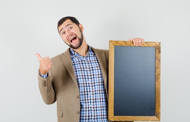 Jeune homme tenant un tableau noir, montrant le pouce vers le haut en chemise, veste et à la gaieté. vue de face.