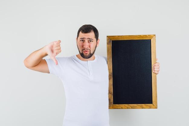 Jeune homme tenant un tableau noir tout en montrant le pouce vers le bas en t-shirt blanc et l'air mécontent, vue de face.