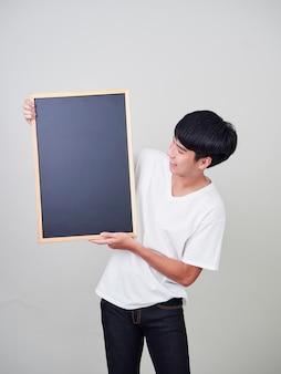 Jeune homme tenant un tableau noir