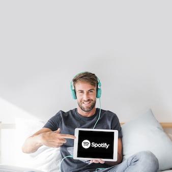 Jeune homme tenant une tablette avec l'application spotify