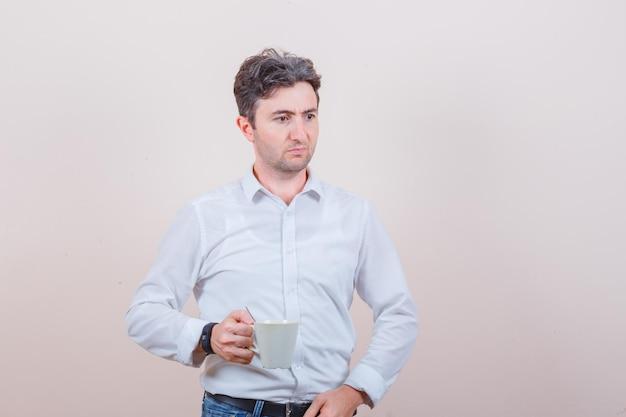 Jeune homme tenant une tasse de boisson en chemise blanche, jeans et à la pensive