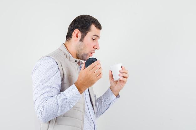Jeune homme tenant une tasse de café à emporter et essayant de l'ouvrir en veste beige et à la recherche concentrée. vue de face.