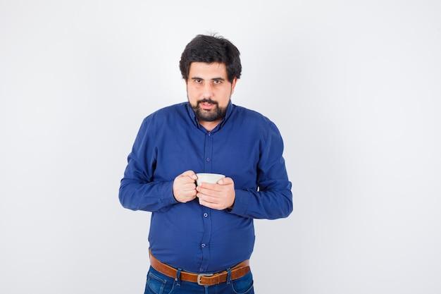 Jeune homme tenant une tasse à deux mains en chemise bleue et jeans et à la recherche de sérieux. vue de face.