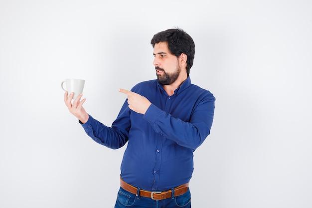 Jeune homme tenant une tasse et pointant vers elle en chemise bleue et jeans et l'air optimiste, vue de face.