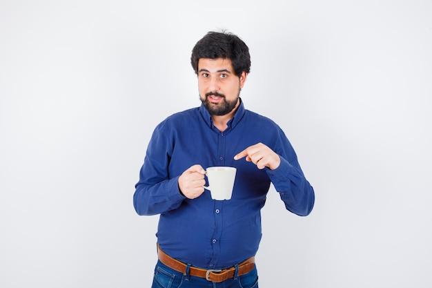 Jeune homme tenant une tasse et pointant vers elle en chemise bleue et jeans et regardant sérieux, vue de face.