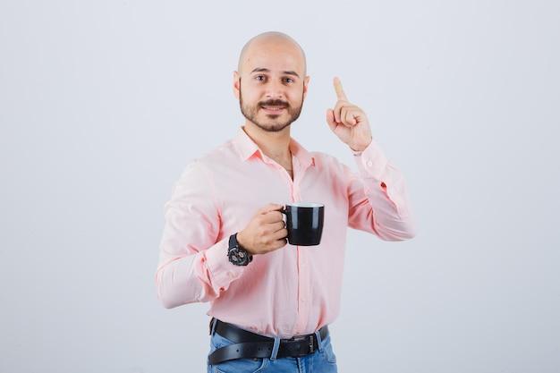 Jeune homme tenant une tasse tout en pointant vers le haut en chemise rose, jeans, vue de face.