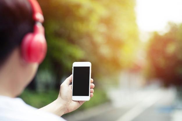 Jeune homme tenant un téléphone intelligent à la main à l'aide d'écouteurs pour écouter de la musique avec un écran vide d'espace copie isolé pour les changements de chanson et de pistes sur mobile. casque profiter du rythme. concept technologique