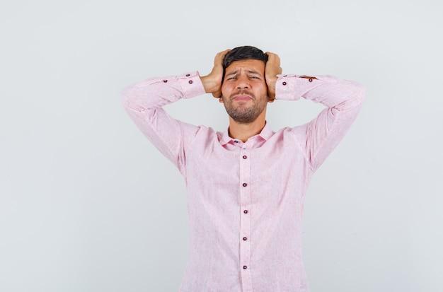 Jeune homme tenant la tête avec les mains en chemise rose et à la recherche de regret. vue de face.