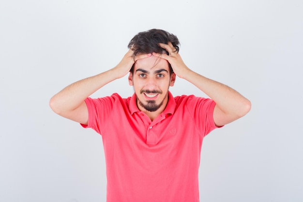 Jeune homme tenant la tête avec les mains en t-shirt rose et l'air confiant. vue de face.