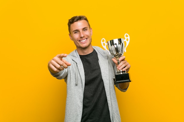 Jeune homme tenant un trophée sourires joyeux pointant vers l'avant