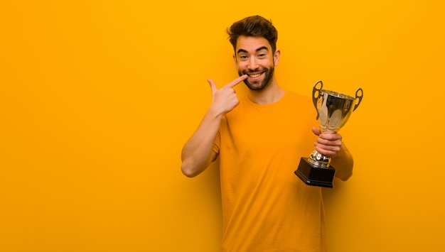Jeune homme tenant un trophée sourit, pointant la bouche