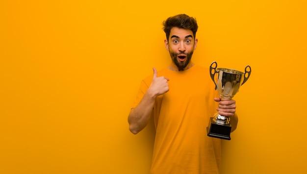 Jeune homme tenant un trophée surpris, se sent prospère et prospère