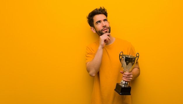 Jeune homme tenant un trophée en train de penser à une idée