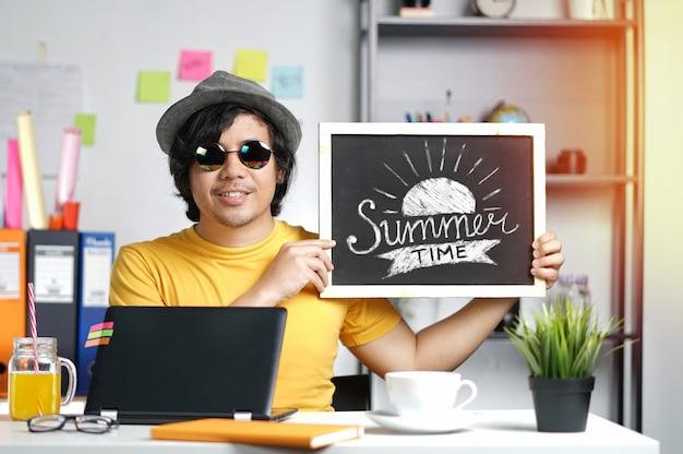 Jeune homme tenant la typographie de l'heure d'été sur tableau noir tout en travaillant