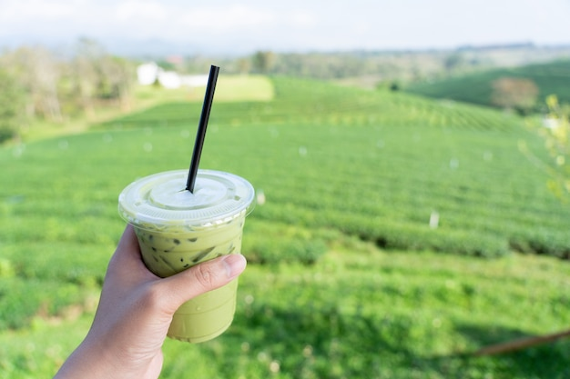 Jeune homme tenant un verre de boisson au thé vert classé avec un grand thé