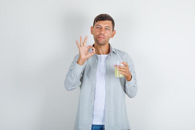 Jeune homme tenant un verre de jus avec signe ok en chemise