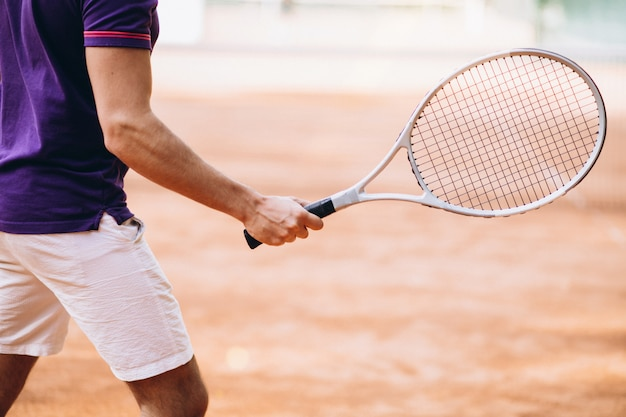 Jeune homme tennisman sur le court, raquette de tennis se bouchent