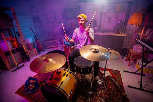 Jeune homme en tenue décontractée, levant les mains avec des baguettes tout en allant frapper des cymbales