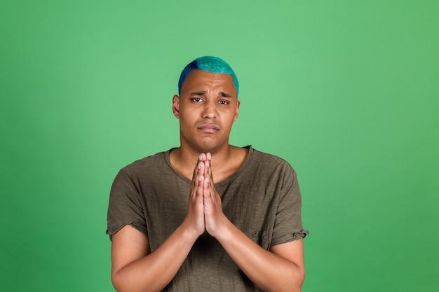 Jeune homme en tenue décontractée sur mur vert cheveux bleus priant avec les mains ensemble