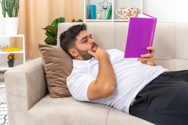 Jeune homme en tenue décontractée tenant un livre avec un visage sérieux passant le week-end à la maison allongé sur un canapé dans un salon lumineux
