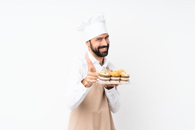 Jeune homme, tenue, gâteau muffin, sur, isolé, pointant devant, et, sourire