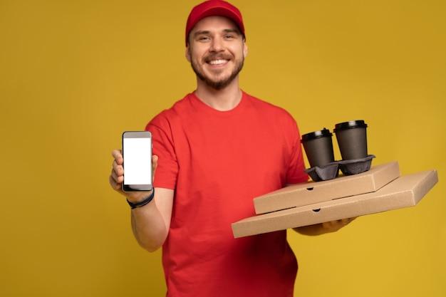 Jeune homme, tenue, pizza, et, smartphone, isolé, sur, mur jaune