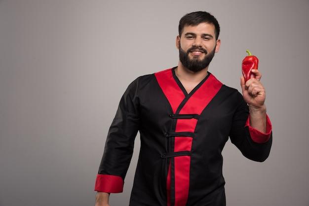 Jeune homme, tenue, poivron rouge, sur, mur gris