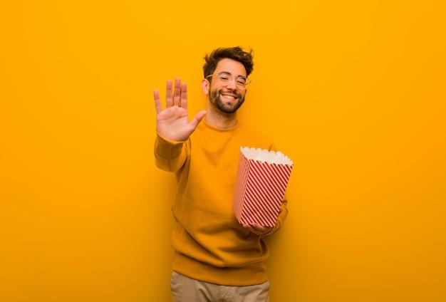 Jeune homme, tenue, pop-corns, mettre, main devant