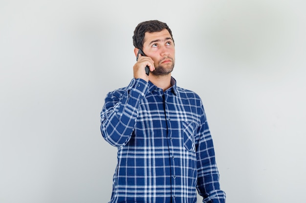 Jeune homme, tenue, smartphone, et, pensée, dans, chemise à carreaux