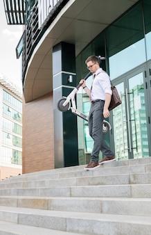 Jeune homme en tenue de soirée avec scooter quittant l'immeuble de bureaux à la fin de la journée de travail et descendant en milieu urbain