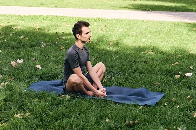 Jeune homme en tenue de sport, faire du yoga dans le parc