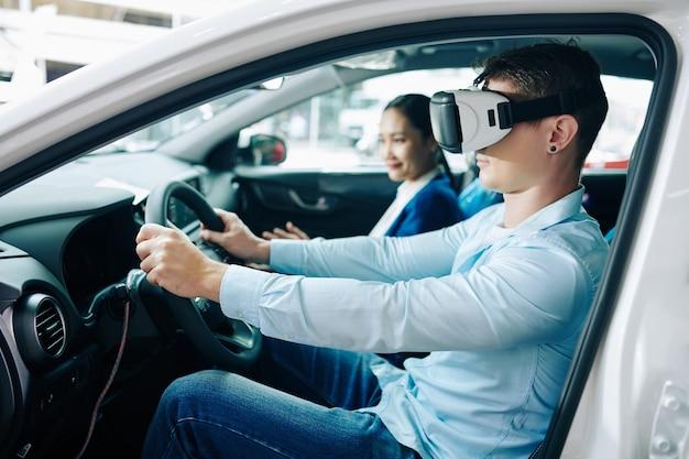 Jeune homme en test de casque de réalité virtuelle au volant d'une nouvelle voiture chez le concessionnaire, directeur assis sur le siège passager