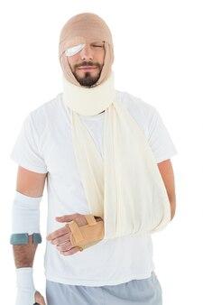Jeune homme avec la tête ligoté dans le bandage et la main cassée