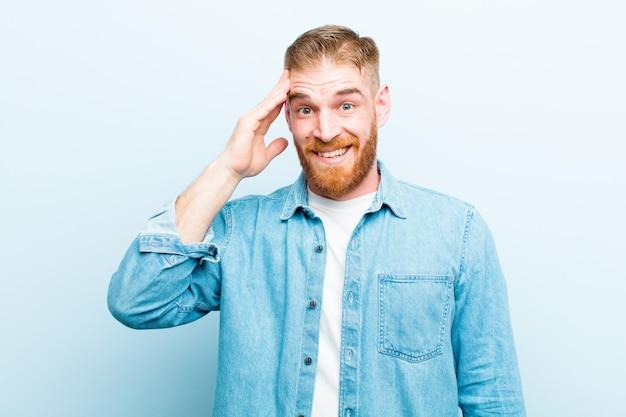 Jeune homme à tête rouge à l'air heureux, étonné et surpris, souriant et réalisant une bonne et incroyable nouvelle contre le mur bleu doux