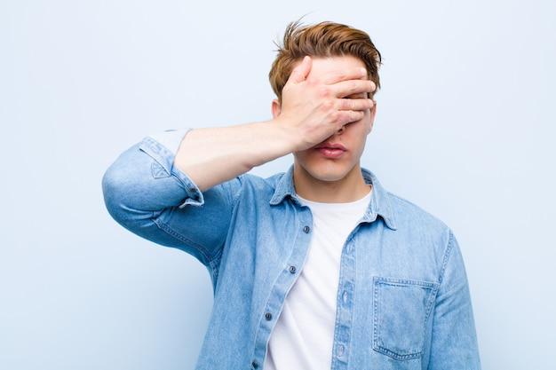 Jeune homme à tête rouge couvrant les yeux d'une main, se sentant effrayé ou anxieux, se demandant ou attendant aveuglément une surprise contre le mur bleu