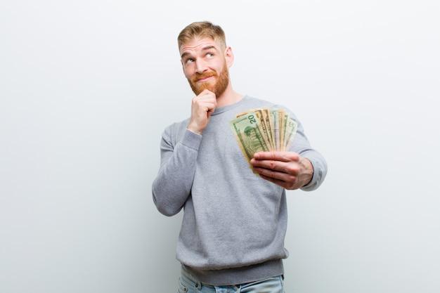 Jeune homme à tête rouge avec des dollars blancs