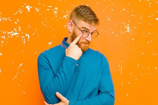 Jeune homme à tête rouge en gardant un œil sur vous, ne pas faire confiance, regarder et rester alerte et vigilant sur le mur orange grunge