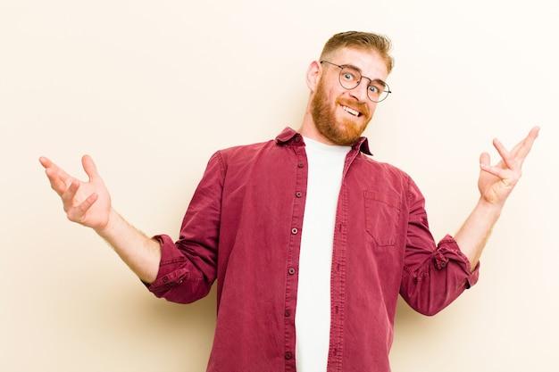 Jeune homme à tête rouge haussant les épaules avec une expression stupide, folle, confuse, perplexe, se sentant agacé et désemparé contre le mur beige