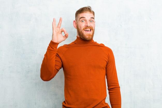 Jeune homme à tête rouge portant le cou de tortue se sentir réussi et satisfait, souriant avec la bouche grande ouverte, faisant signe avec la main contre le mur de ciment
