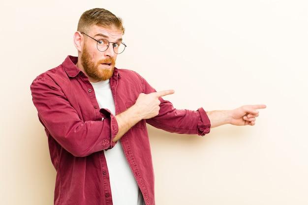 Jeune homme à tête rouge se sentant choqué et surpris, pointant pour copier l'espace sur le côté avec un regard étonné et bouche bée