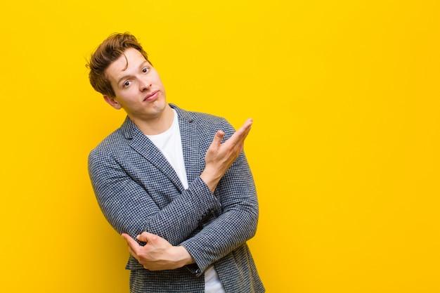 Jeune homme à la tête rouge se sentant confus et désemparé, s'interrogeant sur une explication douteuse pensé orange
